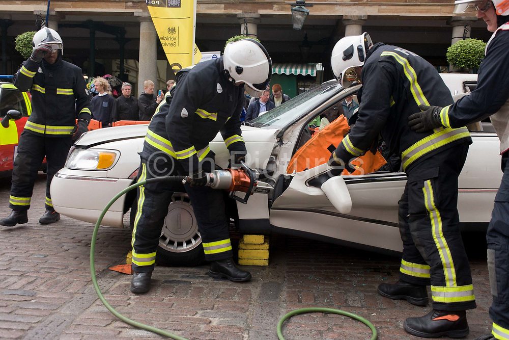 Firefighters from the London Fire Brigade's 'extrication' team using a using a Holmatro dedicated cutter to demonstrate how firefighters rescue passengers by cutting open a stretch limousine in London's Covent Garden Piazza. Highlighting the dangers of hiring illegal luxury or novelty cars, this vehicle was seized last year with many mechanical defects rendering it unsafe for those inside with limited exit doors. Of 358 cars stopped in March 2012, 27 were seized and 232 given prohibitions.