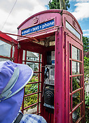 Classic red telephone box in Eskdale, Lake District National Park. England Coast to Coast hike with Wilderness Travel, day 2 of 14: from Eskdale in Cumbria county, we walked to Boot for lunch at a local pub and a visit to a working medieval corn mill, in the United Kingdom, Europe. We then climbed to Burnmoor Tarn, then descended to the hamlet of Wasdale Head. Via minibus we returned to Irton Hall for the second night. [This image, commissioned by Wilderness Travel, is not available to any other agency providing group travel in the UK, but may otherwise be licensable from Tom Dempsey – please inquire at PhotoSeek.com.]
