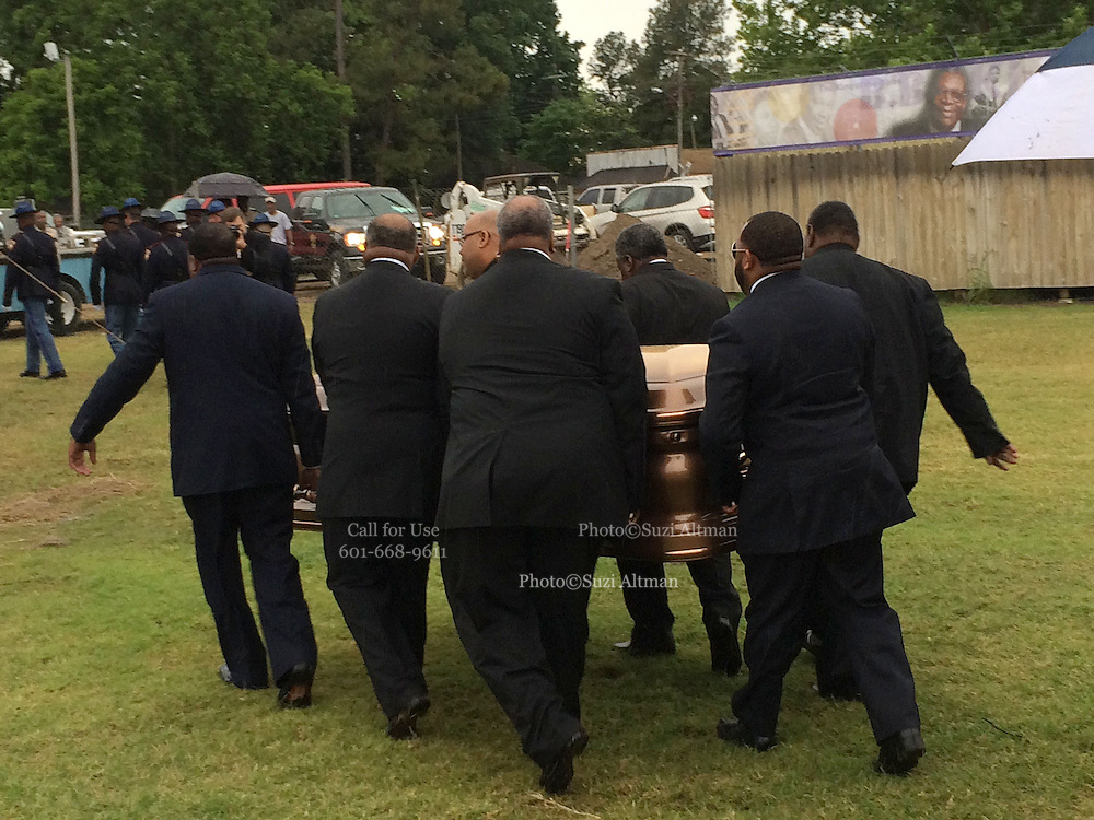 """5/30/15 Indianola, BB Kings band members carry the casket bearing his body to its final resting place outside his museum in Indianola Mississippi. Fans to see B. B Kings final home coming funeral procession outside the BB King Museum. A family member reaches out to touch the casket for one last time at the gravesite of Mr. King during the burial outside in the rain. The Thrill is gone, the casket holding the body of BB King arrives at the Bell Grove Missionary Baptist Church for his final homecoming. Blues legend B.B. King is is laid to rest in the shadow of the cotton gin at the B.B. King Museum and Interpretive Center. Mr King's final homecoming procession included a black horse WITH A saddle flanked with two of BB's famous """"Lucielle"""" guitars signed by Mr. King. Fans lined the streets to watch the procession and pay their respect to the King of the Blues. Photo ©Suzi Altman"""