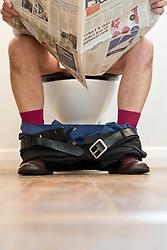 Man Sitting on Toilet Reading Newspaper