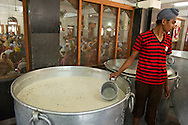 A dessert made of rice, milk, sugar and spices waits to be served to the people dining in the hall in the background.