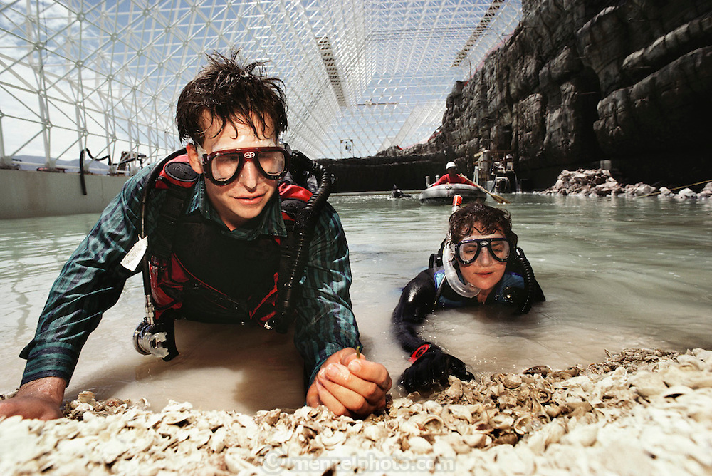 Biosphere 2 Project undertaken by Space Biosphere Ventures, a private ecological research firm funded by Edward P. Bass of Texas.  Biosphere scientists Goga Malich (right) and Taber McCallum seen after diving inside the artificial ocean of the Biosphere 2 Project during construction. The Ocean 'biome' provided a source of fish during the two-year duration of the Project. Water that evaporated from the surface of the 'ocean' was condensed and filtered to provide fresh water for consumption and to replenish the freshwater stream.  Biosphere 2 was a privately funded experiment, designed to investigate the way in which humans interact with a small self-sufficient ecological environment, and to look at possibilities for future planetary colonization.  1990