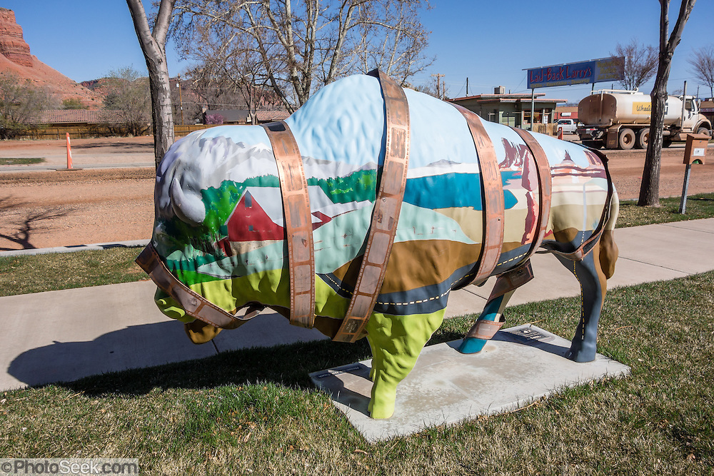 """""""Film Buff,"""" a metal buffalo sculpture by artist Arlene Sibley, is installed at Kane County Information Center (address: 78 S 100 E, Kanab, Utah 84741, USA). Wrapping the buffalo is a film strip listing names of movies filmed in Kanab.  Kanab is home of the USA's first all-woman town council, elected in 1911, with Mary Woolley Chamberlain as mayor."""