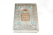 Cutout of a silver bound Holy Bible on white background