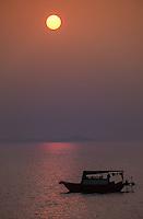 HA LONG BAY, VIETNAM - CIRCA SEPTEMBER 2014:  Fishing boat at sunrise during a foggy morning, in Halong Bay