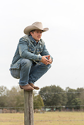 cowboy squatting down on top of a fence pole on a ranch