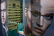An optician's window ad faces and spectacles display in central London. We look through the window of this Soho optometrist's business and see rows of stylish glasses and sunglasses on glass shelves in the background while in the foreground are the large faces of a modern, young and good-looking man and woman both wearing male and female frames.