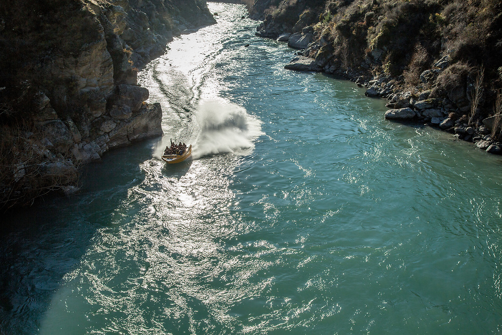 Tourists enjoy Goldfields Jet Boat experience on the Kawarau Gorge between Queenstown and Cromwell, Central Otago, South Island, New Zealand