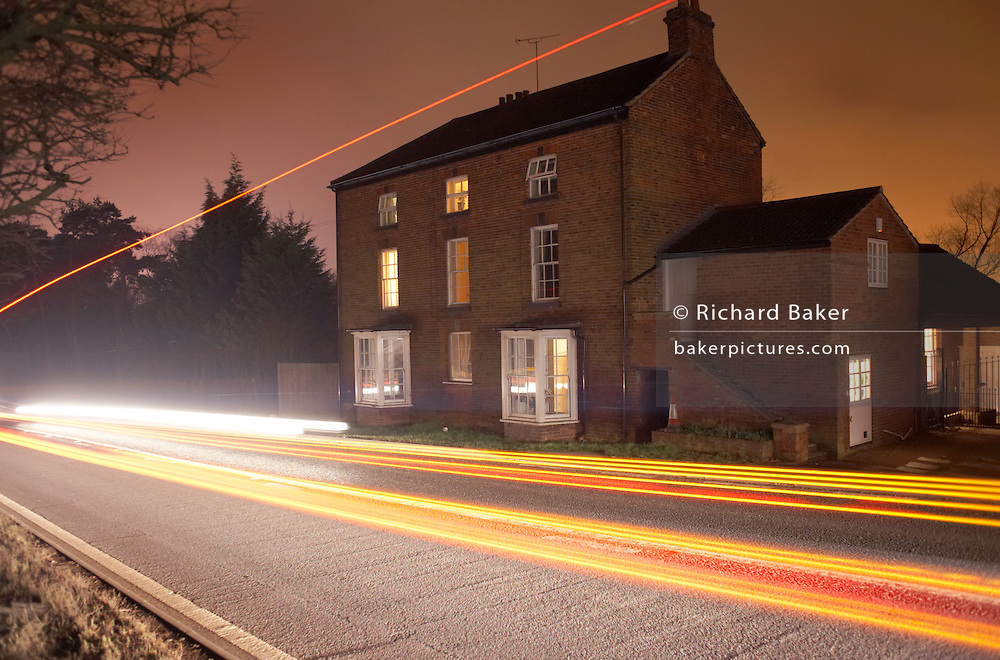 Moving fast past a farmhouse building on a busy UK A road, unseen traffic leaves its light trails on an otherwise dark winter night near the giant DIRFT warehouse logistics park in Daventry, Northamptonshire England. Some rooms are lit in this remote residence which show signs of occupation. Red tail lights from cars, lorries and trucks streak by with tall traces of container traffic leaves light on the picture, diagonally leaving their mark. It is a very busy highway on which to own a home but this infrastructure is a vital route that keeps Britain's logistics moving across the country 24/7.
