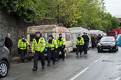 © Licensed to London News Pictures; 20/05/2021; Bristol, UK. Police and bailiffs walk past caravans lining the side of Glenfrome Road after evicting them from squatting on the site of a former gas works belonging to Wales and West. The site was occupied by around 75 people including children mostly living in vehicles and caravans.  Bailiffs brought in a crane to lift people off a scaffold tripod blocking the entrance to the site. Police led some occupants away and released them. The site was evicted last year. Photo credit: Simon Chapman/LNP.