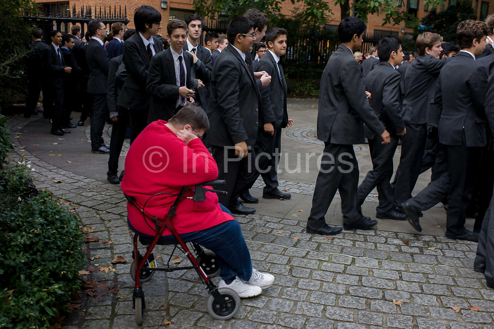 Schoolboys in grey suits walk past resting disabled woman. As the young men file past in a queue to enter St Paul's Cathedral for an event in central London. The lady in red sits in a wheelie seat, seemingly dozing or asleep and unaware of the busy activity all around her. The youths are wearing sober grey suits as part of theirt school or college uniform - all smart boys with fine futures ahead of them.