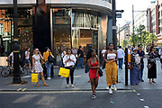 Busy street scene along Oxford Street in London, England, United Kingdom. This is the busiest shopping district in the capital with Oxford Street being the most crowded. Crowds can be so big that many people avoid the area altogether.