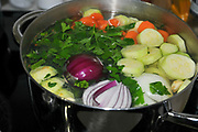Preparing vegetable broth boiling vegetables in a large pot of water