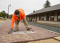 Tony Roy of Stoneage Stone Works fits in the last bricks on a new section of paved walkway for Phase 2 of the Wow Trail at the Lacconia Railroad Station on Tuesday.  (Karen Bobotas/for the Laconia Daily Sun)