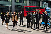 City workers walk across a pedestrian crossing outside Canary Wharf tube station, Docklands, London, United Kingdom.  An iconic Transport for London double decker red bus is in the background. Canary Wharf is a famous financial district.