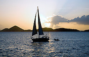 Sailboat and dinghy cruising past Water Island, in the Caribbean Sea.