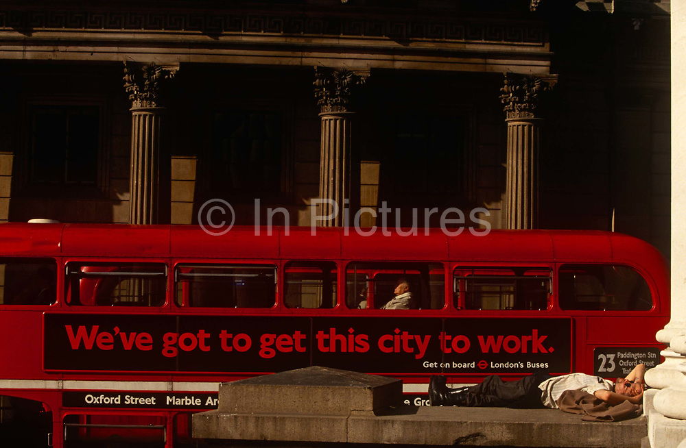 A man sleeps in mid-afternoon sunshine on the steps of Royal Exchange opposite the Bank of England in the City of London, taking a nap in the heart of the capital's financial district. A red double-decker Routemaster bus has stopped in a queue of traffic opposite with an advert for London buses saying 'We've got to get this city to work' but with tattoos on his arms and his forehead and wearing heavy army-style boots, he is clearly not on his way to a job and therefore out-of-place in this busy part of London. With arms folded and head resting on an unseasonal coat, the man is asleep and going nowhere.