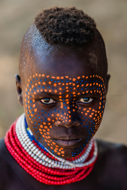 A young Kara tribe woman with elaborately painted face and colored beads in the Dus village above the Omo River, Omo Valley, Ethiopia.