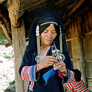 An Aini ethnic minority woman sewing her traditional clothing outside her home in Xiang Dao Ya village. Costume styles in the past were identified by discrete regions and sub regions, but due to a number of factors some groups are more widely dispersed.  This may be due to migration or search for land, and more recently, as a result of re-settlement of groups by the Chinese government, made necessary by the construction of new roads, reservoirs and hydroelectric schemes. The People's Republic of China recognises 55 ethnic minority groups in China in addition to the Han majority. The ethnic minorities form 9.44% of mainland China and Taiwan's total population and the greatest number can be found in Yunnan Province, 34% (25 ethnic groups).