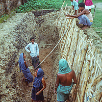 Homeless people dig a latrine for their neighbors at Mirpur Destitute Camp near Dhaka, Bangladesh, a population left homeless after a cyclone and 1971 war of indepence.