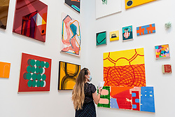 © Licensed to London News Pictures. 15/09/2021. LONDON, UK. A woman looks at 'RED CHAIR' by Stephen Cooper, price £4000. Preview of the Summer Exhibition 2021 at the Royal Academy of Arts in Piccadilly. Co-ordinated by Yinka Shonibare RA, the exhibition explores the theme of 'Reclaiming Magic' to celebrate the joy of creating art with around 1400 works by emerging and established artists featured in the exhibition.  The Summer Exhibition is the world's largest open submission contemporary art show and has taken place every year without interruption since 1769.  Photo credit: Stephen Chung/LNP