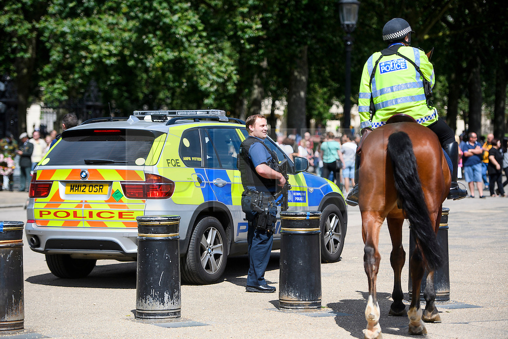 © Licensed to London News Pictures. 16/07/2016. London, UK. Armed and mounted police watch over a parade on Horseguards Parade in Westminster, London two days after more than 80 people were killed in a terrorist attack in Nice, southern France. Photo credit: Ben Cawthra/LNP
