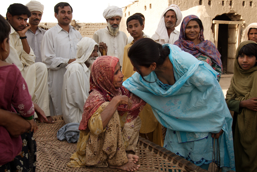 """Asia Perveen, a social worker with the Human Rights Commission in Multan, meets with the family of sisters Tasleem and Zubada, Dera, Pakistan, April 26, 2005. The two were gang raped by neighbors who felt they were dishonored by Zubada's son Naeem. """"I want them to be punished,"""" said Tasleem. """"They are our enemies, I will be afraid until they are hanged publicly."""""""