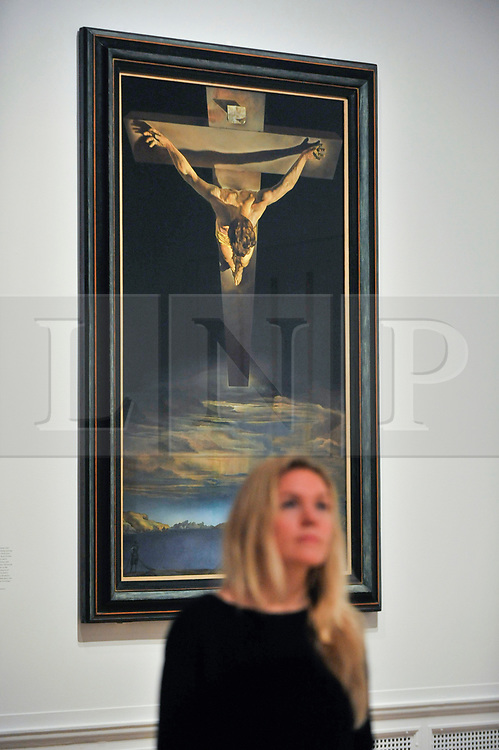 "© Licensed to London News Pictures. 03/10/2017. London, UK.  A staff member in front of ""Christ of Saint John of the Cross"", 1951, by Salvador Dali at the preview of ""Dali / Duchamp"", a new exhibition of works by Salvador Dali and Michel Duchamp taking place at the Royal Academy of Arts in Piccadilly.  Over 80 artworks in different media are on display from 7 October to 3 January 2018.   Photo credit : Stephen Chung/LNP"