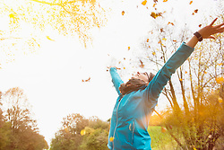 Woman laughing while throwing autumn leaves in air