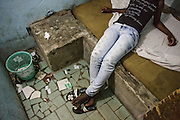 Lucie, 15, lies on a bed in one of the rooms where she meets clients in a brothel in Abidjan, Cote d'Ivoire on Wednesday July 17, 2013. Lucie left her father's home in northwestern Cote d'Ivoire because she couldn't get along with his third wife. She would prefer working in home cleaning, but has no references and no one will hire her. She says she's had unprotected sex with clients only 3 times, at the client's request. On those occasions, she charged 2000 CFA (4$) instead of the usual 1000. Lucie has never been to school.