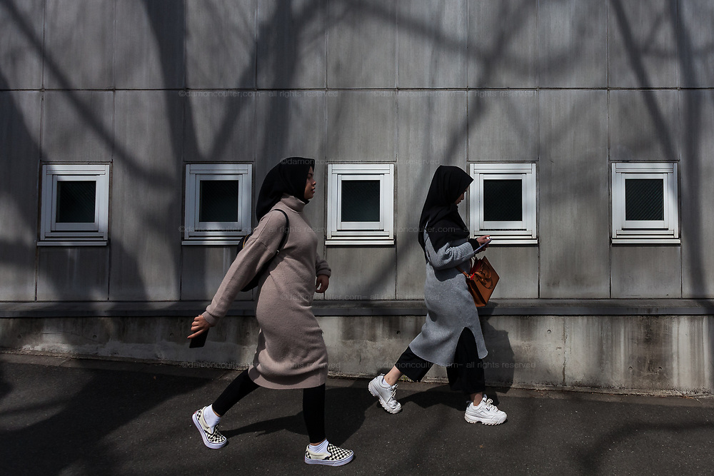 Two young  Muslim immigrant women, wearing hijab, walk near the Tokyo Camii mosque in Yoyogi Uehara, Tokyo, Japan. Friday March 22nd 2019.   The Tokyo Camii Mosque is the largest mosque in Japan where estimate currently put the immigrant and native population of Muslims at around 130,000.