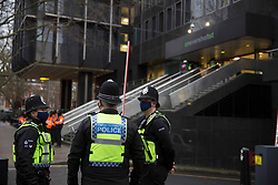 © Licensed to London News Pictures. 03/02/2021. London,UK. Police guard the offices of HS2 as bailiffs work to evict a group of eco-activists who are living in increasingly unstable tunnels beneath Euston Square Gardens in central London. The eviction of the HS2 Rebellion group from the square began one week ago and continues today.  Photo credit: Marcin Nowak/LNP