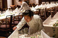 Young woman working at laying tables for an upmarket dinner.