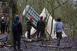 Harefield, UK. 14 January, 2020. Stop HS2 activists remove their belongings as enforcement agents working on behalf of HS2 attempt to evict activists from a protection camp close to Harvil Road. Part of the nearby Colne Valley protection camp was evicted by bailiffs last week. 108 ancient woodlands are set to be destroyed by the high-speed rail link and further destruction of trees for HS2 in the Harvil Road area is believed to be imminent.