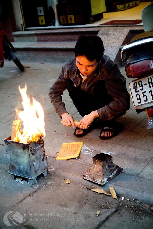 VIetnamese man offering prayers on the streets of Hanoi.