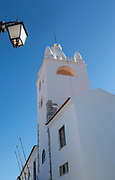 Looking up at deep blue sky and whitewashed church tower Torre Do Bem Relogio, village of Alvito, Baixo Alentejo, Portugal, southern Europe