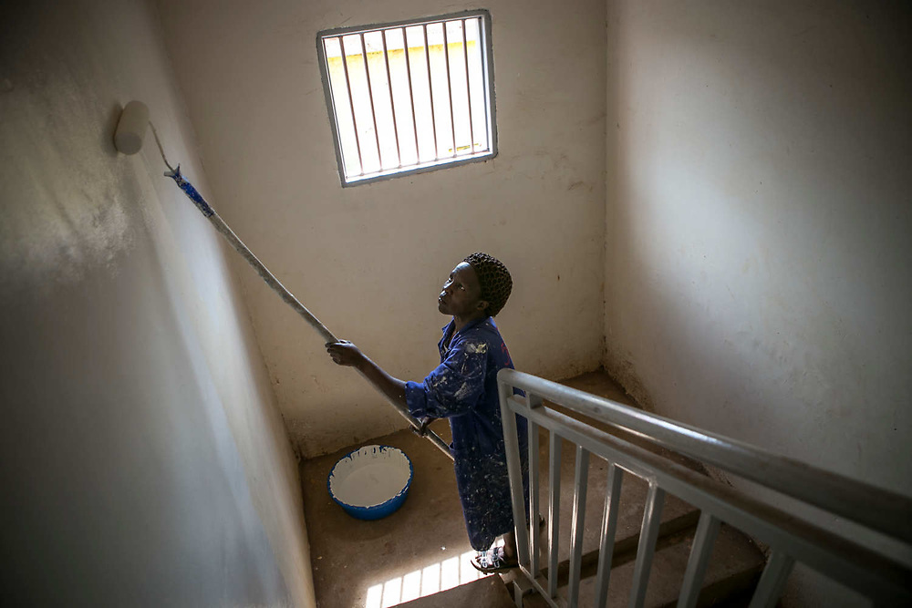 Acheng Irine, a former sex slave of LRA, paints the wall of a hotel in Gulu, Uganda, October, 2017. She was abducted by LRA forces in the middle of the night when she was about 13 years old at St. Mary's school and was assigned to a commander six months later. She became the 7th wife and gave birth to one daughter who is now 25 years old.