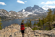 A backpacker soaks in the view of Garnet Lake with Banner Peak in the background; Ansel Adams Wilderness, Inyo National Forest, Sierra Nevada Mountains, California, USA.