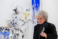 """© Licensed to London News Pictures. 14/10/2020. LONDON, UK. Artist Maggi Hambling poses with her work """"Self portrait, working"""", 2020, at the preview of Maggi Hambling: 2020 at Malborough Gallery in Mayfair.  The exhibition of recent paintings coincides with Hambling's 75th Birthday and runs 15 October to 21 November 2020.  Photo credit: Stephen Chung/LNP"""