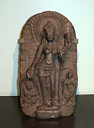 Tara 1100-1200 Bihar, North-East India, Basalt.  The name Tara means 'saviouress'.  She is a goddess widely worshipped for her protective powers and compassionate nature.  Here she holds a lotus in one hand and makes the gesture of granting wishes with the other.  The architectural composition, with Tara standing against an elaborate throne back, suggests that the relief was a miniature shrine.