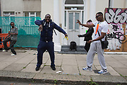 Group of guys dancing to music at I Spy The People sound system on Colville Gardens. Notting Hill Carnival in West London. A celebration of West Indian / Caribbean culture and Europe's largest street party, festival and parade. Revellers come in their hundreds of thousands to have fun, dance, drink and let go in the brilliant atmosphere. It is led by members of the West Indian / Caribbrean community, particularly the Trinidadian and Tobagonian British population, many of whom have lived in the area since the 1950s. The carnival has attracted up to 2 million people in the past and centres around a parade of floats, dancers and sound systems.