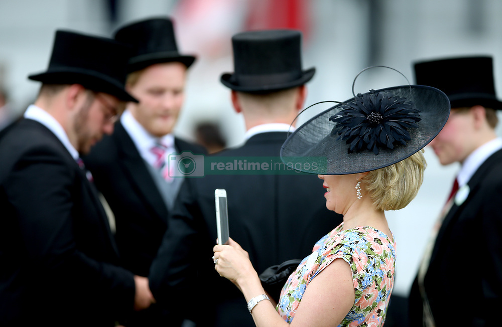 A racegoer takes a photo on her phone during day five of Royal Ascot at Ascot Racecourse.
