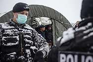 Migrants are seen outside a tent monitored by the police during a visit of local authorities. A heavy snowfall on the camp of Lipa, Bosnia Herzegovina, January 25, 2021.
