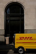 A DHL courier van makes a delivery and is parked in a side street in the City of London.