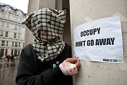"© licensed to London News Pictures. London, UK 22/02/2012. An Occupy London protester is pictured next to a sign which reads ""Occupy won't go away"" as the protest group lost their court case and refused permission to appeal against their eviction from the Occupy London camp outside St Paul's Cathedral. Photo credit: Tolga Akmen/LNP"