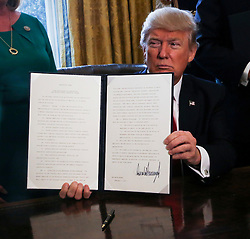Washington, DC - February 3, 2017; U.S. President Donald Trump signs Executive Orders in the Oval Office of the White House, including an order to review the Dodd-Frank Wall Street to roll back financial regulations of the Obama era.