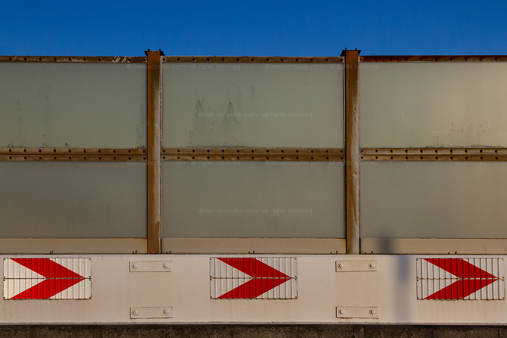 Arrows on a crash barrier below glass soundproofing walls on a road in Tokyo, Japan. Sunday March14th 2021