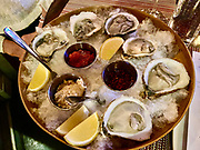 Platter of raw oysters with three sauces and lemon slices on a bed of ice