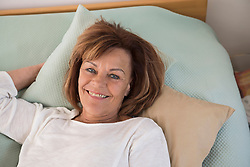 Portrait of senior woman lying on bed and smiling, Munich, Bavaria, Germany
