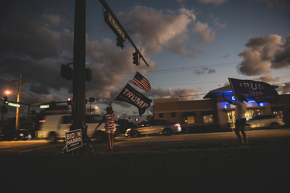 With four minutes to go before polls close, Barbara Daigle and Lee Guthrie stand with Trump 2020 flags beside Highway 192 in Indialantic, Florida. (November 3, 2020)